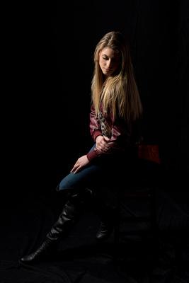 High School Girl Senior portrait in-studio on a black backdrop